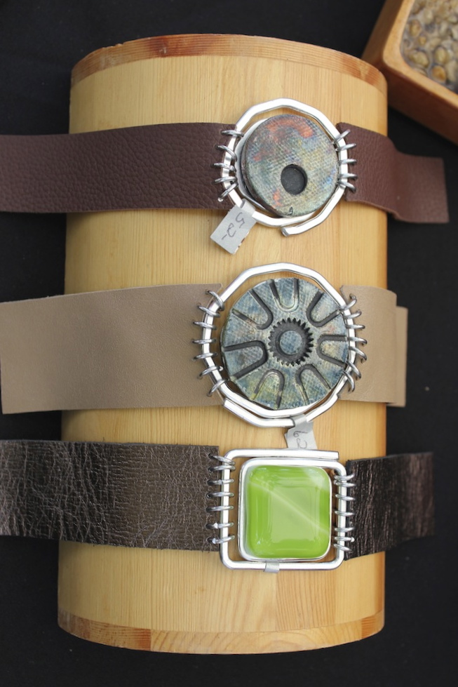 Aluminum, fused glass and leather bracelets.