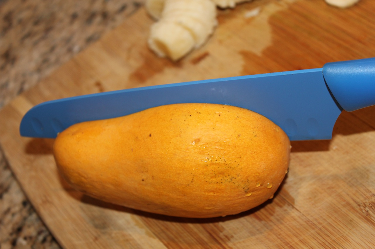 Cut mango lengthwise on one side. The bone is in the middle; it is long and flat.