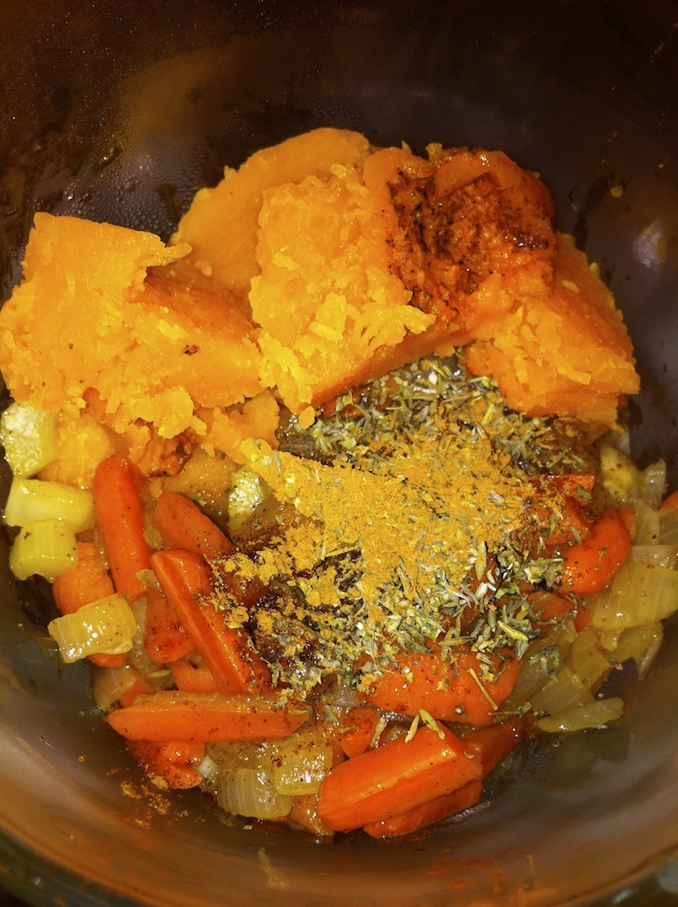 Adding sauteed veggies and spices to the squash.