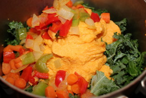 Adding sauteed veggies and processed cooked sweet potato and cashews to the main pot.
